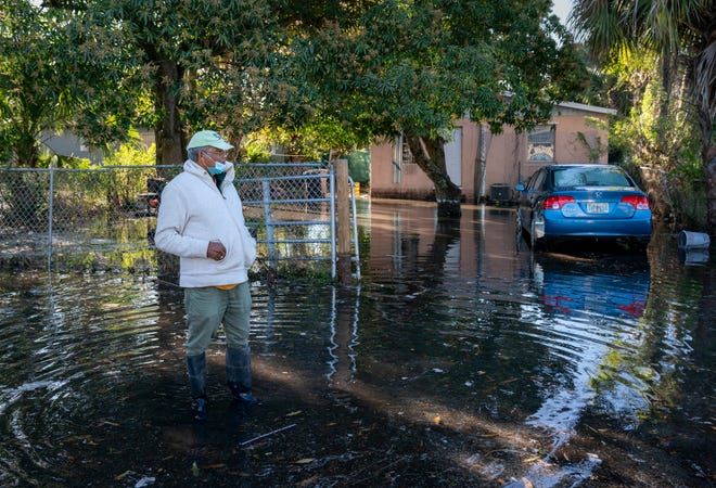 Petamber Dindiyal wades through the water in front of his house after a water main break flooded his front yard near the 600 block of Tamarind Avenue in West Palm Beach on Friday. GREG LOVETT/PALM BEACH POST