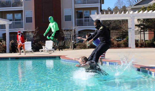 Petersburg Police Department's Finest 2021 Polar Plunge team plunge into the 1200 Acqua Apartments' pool in Petersburg to raise money for Special Olympics Virginia on Feb. 4, 2021. Chief Travis Christian jumps in wearing his uniform.