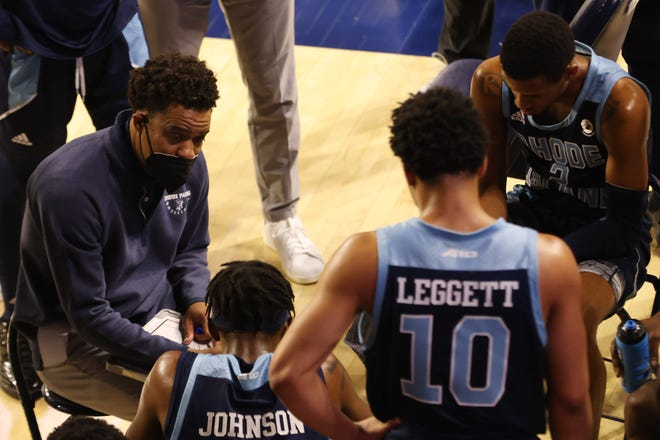 URI head coach David Cox, left, talks to his team in a huddle during a timeout against the Richmond Spiders in the first half of a January game at the Robins Center.