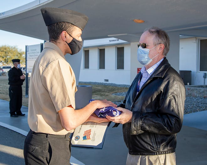 Keith Wheeler receives a flag flown in his honor at Naval Air Weapons Station China Lake, California, to mark the end of his 38-year federal service career.