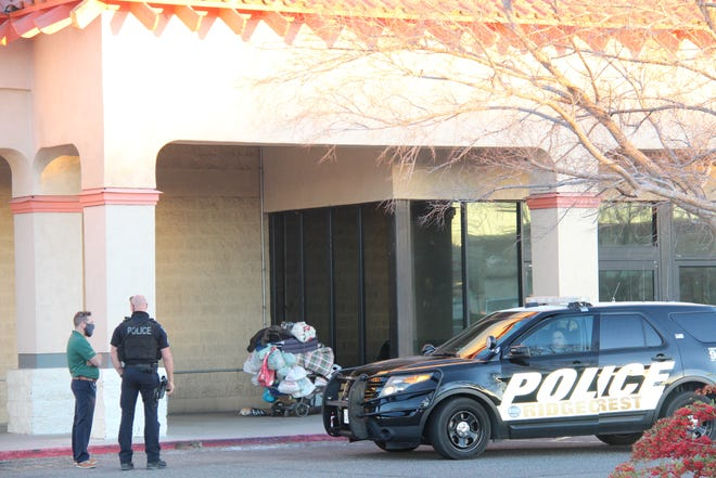 An RPD officer and another man wait outside the old Kmart building on China Lake Boulevard on Feb. 5, 2021, after RPD arrested a transient woman on a charge of trespassing when she reportedly refused to leave the property.