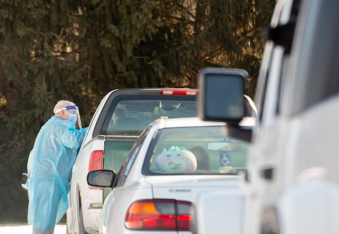 Kent Huffman of VISIT Health Care gives Coronavirus tests during a testing clinic at Midway Drive-In on Route 59 in Ravenna Township.