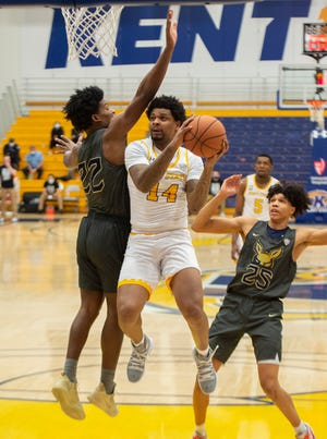 Kent State's Tervell Beck takes a shot against the University of Akron's Mikal Dawson and Enrique Freeman during the Zips' 72-61 win over the Golden Flashes on Friday night at the M.A.C. Center. [Lisa Scalfaro/Record Courier]
