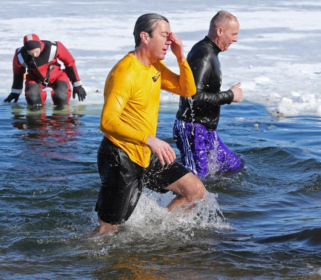 Justin Hardesty, president of Jackson Local Schools Foundation, reacts to the cold water during the Polar Bear Plunge in Jackson Township on Saturday. In the background is Chris Goff, Jackson Local Schools board of education member.