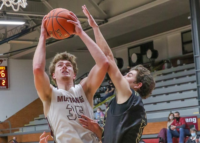 Salina Central forward Caden Kickhaefer (35) grabs a rebound and is fouled by Andover Central's Brock Stupka (5) as he goes up for the shot Friday at the Central gym.