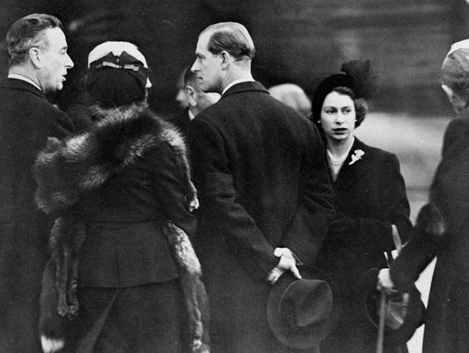 Britain's Queen Elizabeth II, right, and her husband Prince Philip, the Duke of Edinburgh, center with back to camera, are greeted on their arrival at London Airport, on Feb. 7, 1952. The royal couple cut short their official trip to Kenya and returned home following the death of King George VI. Prince Philip is talking to Earl Louis Mountbatten of Burma, left.