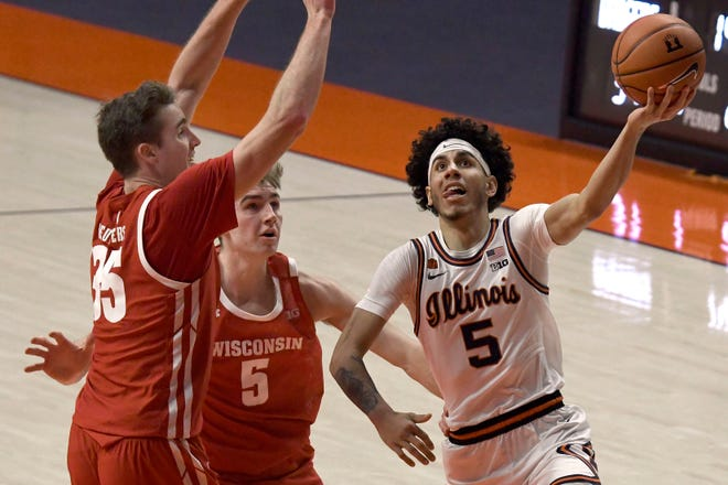 Illinois guard Andre Curbelo (5) drives to the basket as Wisconsin's forward Nate Reuvers (35) and forward Tyler Wahl (5) defend Saturday in Champaign. [Holly Hart/The Associated Press]