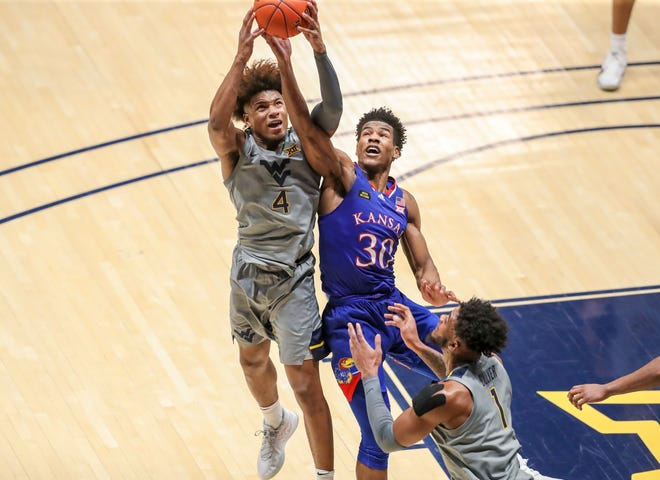 Kansas basketball's Ochai Agbaji, right, and West Virginia's Miles McBride jump for a rebound during Saturday's game at WVU Coliseum in Morgantown, W.Va. McBride finished with 29 points, eight assists, seven rebounds and three steals in the No. 17-ranked Mountaineers' 91-79 victory over the No. 23 Jayhawks.