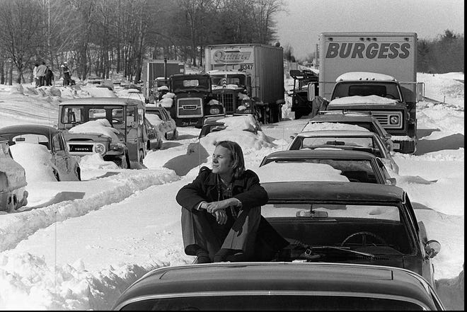 Roy Sodersjerna of Hingham, suns himself on the hood of his car stuck in snow on Massachusetts Route 128 in Dedham. in this Feb. 9, 1978 file photo. Sodersjerna, who waits for plows and tow trucks to dig him out, has been living at a Red Cross shelter nearby since being trapped in the storm three days earlier.