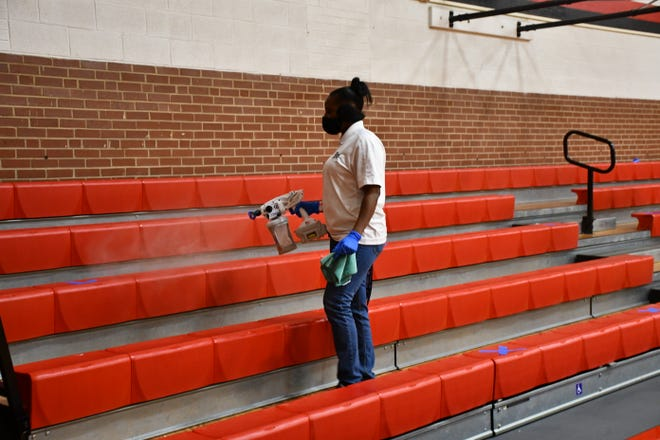 A Graham essential staff worker sprays the gym bleachers with a fogger machine in between basketball games.