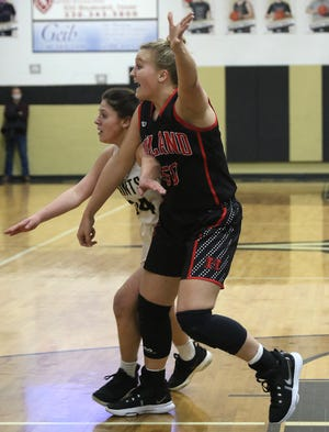 Hiland's Zoe Miller looks for the ball with Tuscarawas Central Catholic's Gina Sciarretti defending in the IVC Girls Basketball Showcase game Saturday