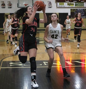 Hiland's Kelsey Swihart drives the ball to the basket with Tuscarawas Central Catholic's Maddie Ferrell defending in the IVC Girls Basketball Showcase game Saturday.