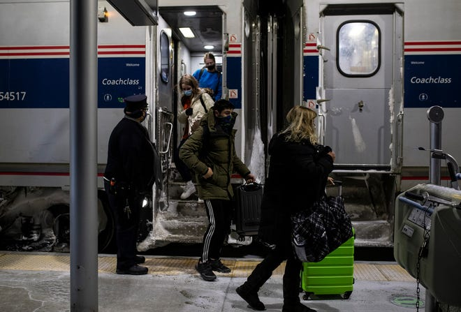 Passengers get off the Amtrak train at the Troy Transit Center in Michigan on Feb. 5. Amtrak mandated masks for all passengers and employees last spring and monitors where passengers sit and how many board each car.