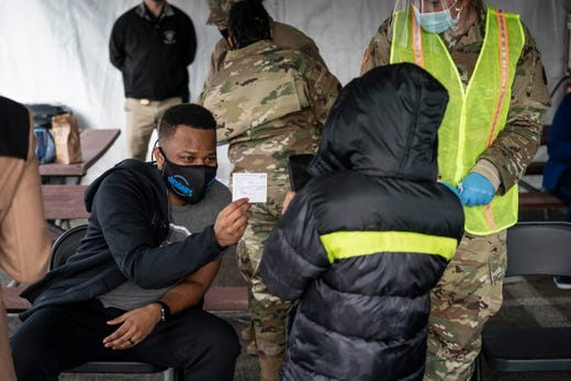 A man shows off his coronavirus vaccine record card to a live stream video in the parking lot of Six Flags on February 6, 2021 in Bowie, Maryland.