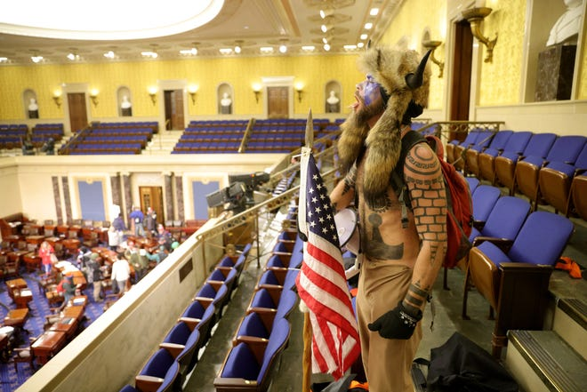A man yells inside the Senate chamber on Jan. 6. On Tuesday, in the same room, lawmakers will hold an impeachment trial of former President Donald Trump, who is charged with inciting the mob.