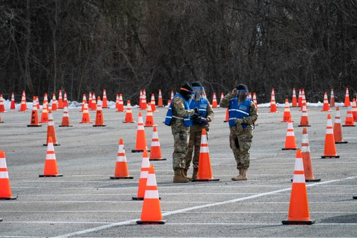 Members of the National Guard wait to check in people at a mass coronavirus vaccination site in the parking lot of Six Flags on February 6, 2021 in Bowie, Maryland.