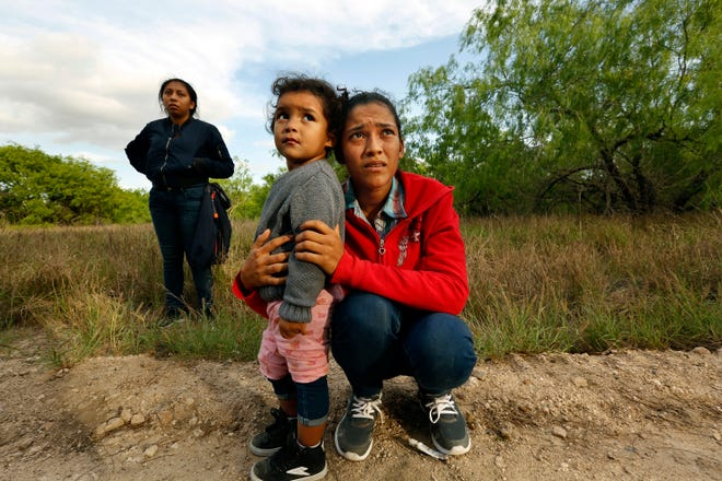 Lirio Funes, 20, holds onto her daughter Melissa Funes, 2, after being detained by local officials after crossing the U.S. - Mexico border in 2018 in McAllen. [Carolyn Cole/Los Angeles Times/TNS]