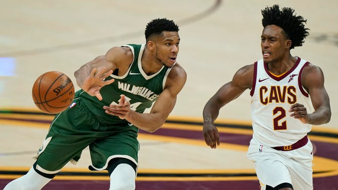 Milwaukee Bucks' Giannis Antetokounmpo (34) passes against Cleveland Cavaliers' Collin Sexton (2) in the first half of an NBA basketball game, Saturday, Feb. 6, 2021, in Cleveland. (AP Photo/Tony Dejak)
