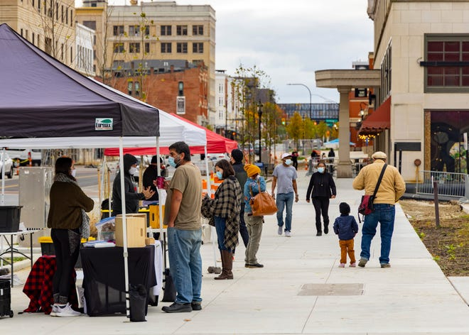 Visitors to downtown Akron stop at pop-up tents at the top of the hill overlooking Lock 3.