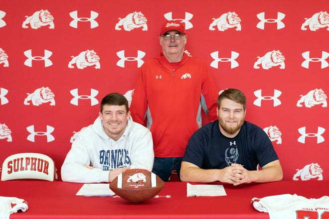 Sulphur seniors Logan Smith, left, and Garrett Trett pose for a photo with Bulldogs head coach Jim Dixon. Smith signed to play football at University of Central Oklahoma, while Trett will continue his career at Southwestern Oklahoma State University.