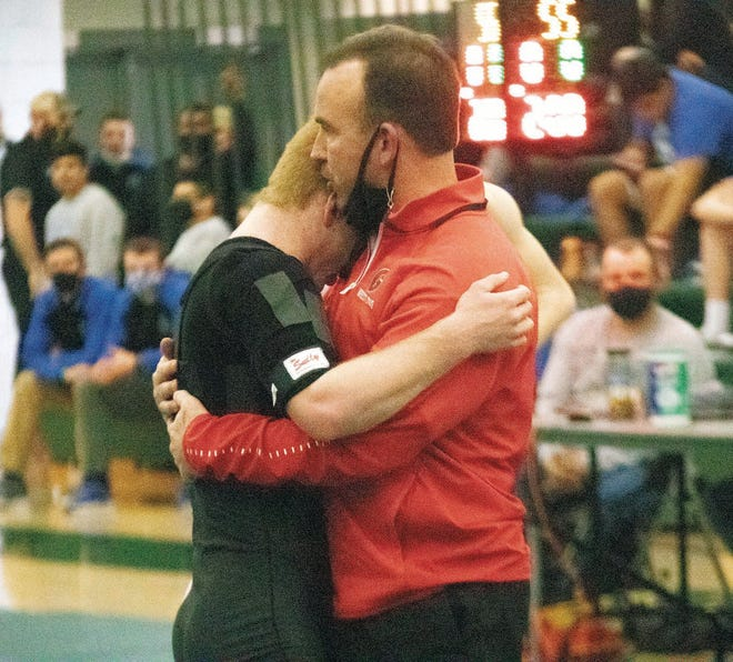 Gilbert head coach Scott Auderer embraces Tiger wrestler Cael Ihle following a match at the Class 2A sectional meet in Woodward Saturday. Ihle took first at 126 pounds as one of five Tigers to advance to districts.