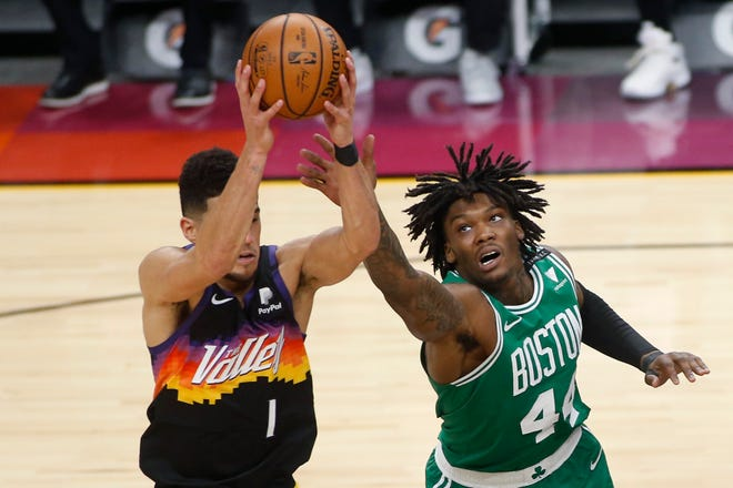 Celtics forward Robert Williams reaches to knock the ball away from Suns guard Devin Booker on Sunday in Phoenix.