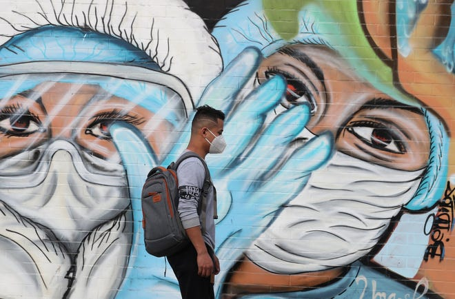 A pedestrian walks past a mural promoting the use of protective face masks to help curb the spread of COVID-19 in Quito, Ecuador, Saturday, Feb. 6, 2021.