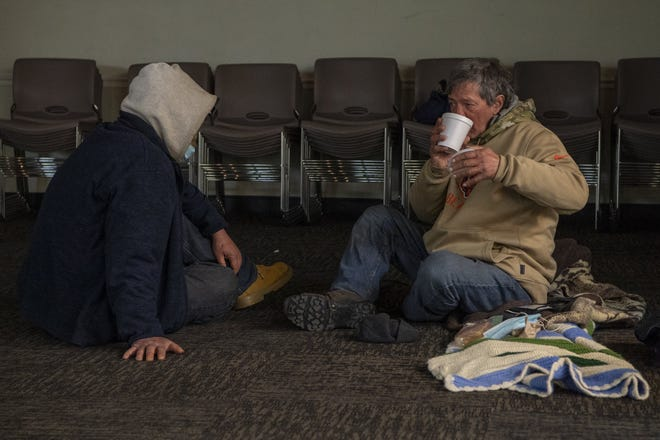Friends Jeff Ratliff, left, and Tim Cape chat a little bit and eat chili after arriving separately for the United Methodist Church For All People's all-night vigil for anyone without a home so they can stay warm during the frigid stretches of winter in Columbus, Ohio, on Feb. 5, 2021.