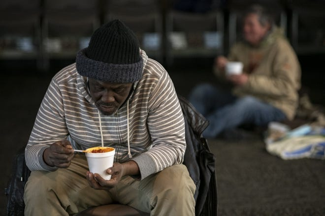 Darrell Newby enjoys chili and a sandwich inside the United Methodist Church For All People during an all-night vigil in February, held for anyone without a home so they could stay warm during a frigid stretch of winter.