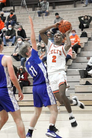 Meadowbrook senior Jonah McCall (2) goes up for a shot over Cambridge's Colton Slaughter (11) during Saturday night's Guernsey County tussle at Meadowbrook High School.