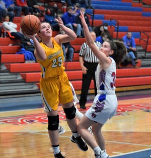 Brooklyn Troyer goes up for two over West Holmes defender Katie Sprang during the Golden Bears' win over the Knights Saturday in The Dungeon.  Troyer poured in a game-high 19 to lead the Bears to their 19th win of the season.