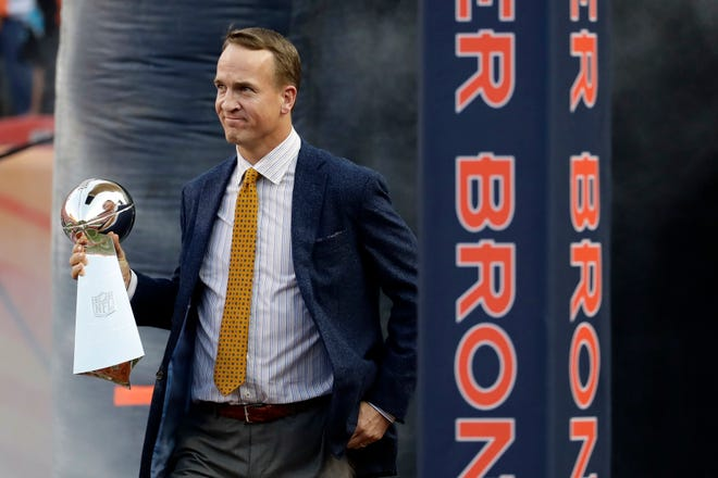 Former Denver Broncos quarterback Peyton Manning carries the Vince Lombardi Trophy from Super Bowl 50 onto the field prior to an NFL football game against the Carolina Panthers in Denver, in this Thursday, Sept. 8, 2016, file photo. Manning was selected Saturday, Feb. 6, 2021, for induction into the Pro Football Hall of Fame's Class of 2021. (AP Photo/Jack Dempsey, File)