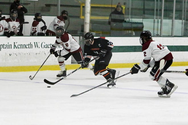 Gardner/Murdock senior defenseman Nick Stone skates the puck up the ice between Fitchburg/Monty Tech's Cole Howard (10) and Max Beaulac (12) during their game at the Wallace Civic Center on Saturday, Feb. 6, 2021.