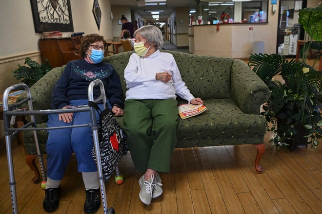 Carmela Sileo, left, and Susan McEachern sit next to each other and talk in the dayroom Feb. 3, 2021 at Arbor Springs Health and Rehabilitation Center in Opelika, Ala. Coronavirus cases have dropped at U.S. nursing homes and other long-term care centers over the past few weeks, offering a glimmer of hope that studies and health officials link to various factors, including the start of vaccinations, the easing of a post-holiday virus surge and better prevention. (AP Photo/Julie Bennett)