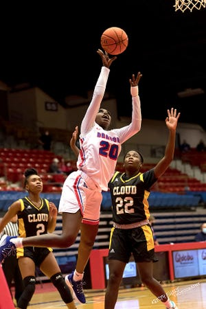 Hutchinson Community College's Lojong Gore (20) shoiots the basket past Cloud County's Sydni Keys (2) and Idalis Lee (22) during their game Saturday night at the Sports Arena. HCC defeated Cloud County 76-44.