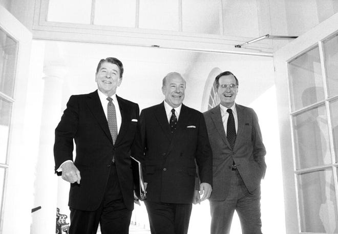 Secretary of State George Shultz, center, walks with President Ronald Reagan and Vice President George Bush in 1985 upon his arrival at the White House in Washington, after two days of arms talks with the Soviet Union in Geneva.