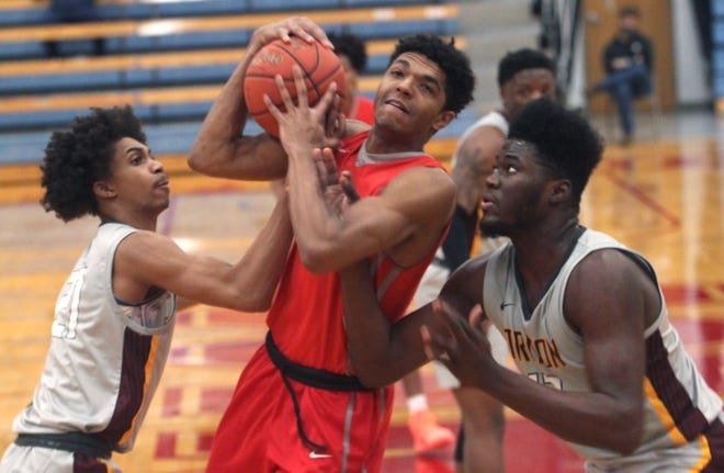 Moberly Area Community College sophomore transfer Quincy Trammell (with ball) gets handcuffed by Triton College's Teonta McKeithen (left) and Deangelo Elisee on Saturday. Trammell made three free throws in the Greyhounds 81-76 loss to the Trojans.