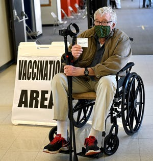 Patrick Dunne, 78, of Framingham, poses with his vaccination card after receiving the Moderna COVID-19 vaccine at Keefe Tech, Feb. 6, 2021.