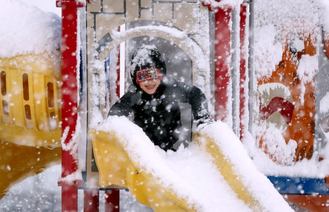 Julian Marzullo, 5, of East Providence, gets in a little light sliding in heavy snowfall at the Hennessy Elementary School playground. He took in the snow and slide courtesy of his mom, Jessica.