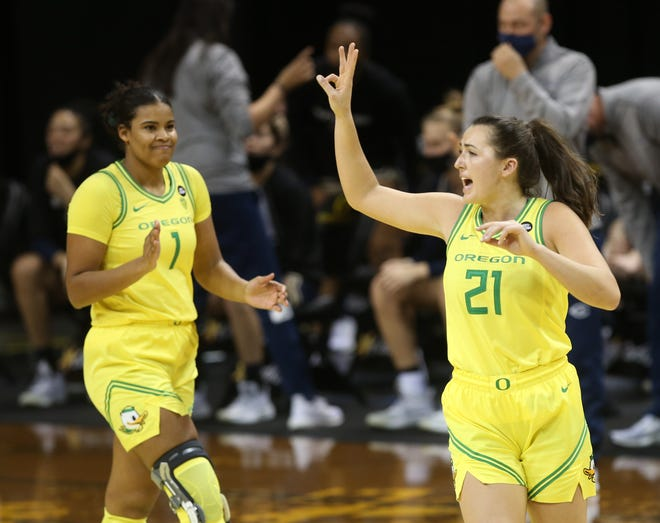 Oregon's Nyara Sabally, left, and Erin Boley celebrate a shot against UC Davis during the first half of their game Saturday, Feb. 6, 2021.