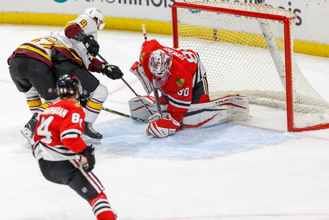 Rockford IceHogs goalie Matt Tomkins goes down to make a save Saturday, but the Chicago Wolves pulled out the 5-4 win in the teams' season opener in Rockford.