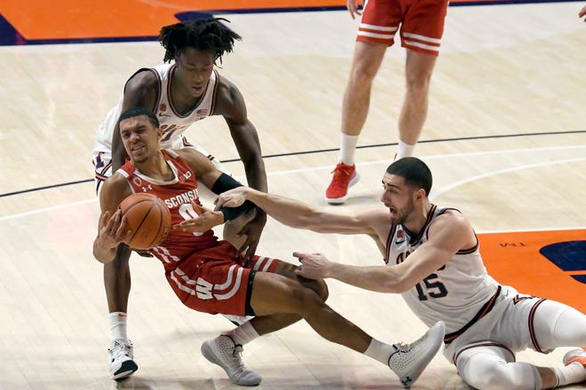 Wisconsin's guard D'Mitrik Trice (0) battles for ball control with Illinois guard Ayo Dosunmu and forward Giorgi Bezhanishvili (15) in the first half Saturday in Champaign.