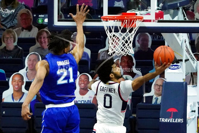 Connecticut's Jalen Gaffney (0) makes a basket against Seton Hall center Ike Obiagu (21) during the second half of an NCAA college basketball game, Saturday, Feb. 6, 2021, at Harry A. Gampel Pavilion in Storrs, Conn.