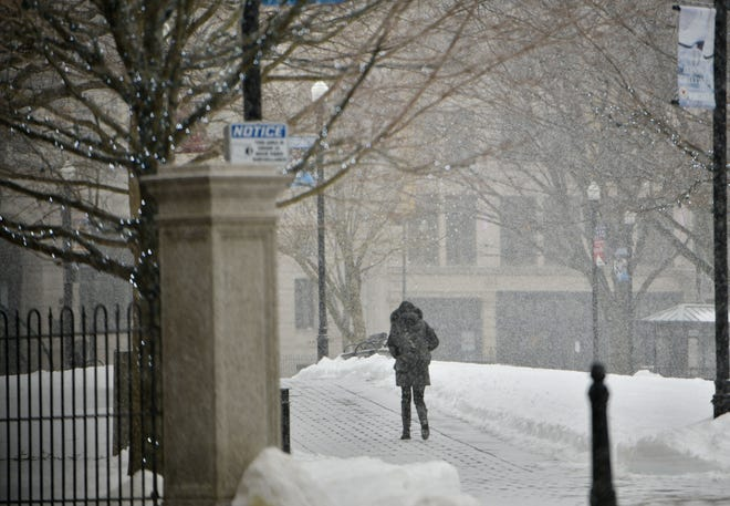 A pedestrian makes her way through heavy snow in downtown Worcester on Sunday.