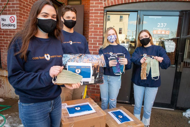 Cold Feet Warm Hearts student volunteers Kait Schuster, left, Hunter Stofer, Grace Lautz and Sarah Lautz hold some of the donated items bound for a homeless shelter Saturday in Worcester.