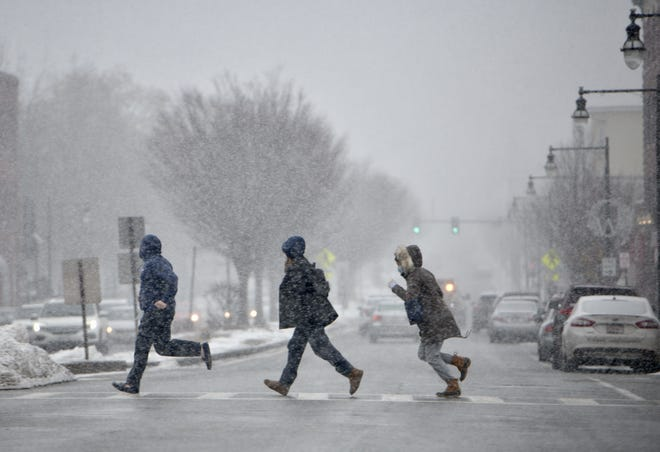 People jog across Shrewsbury and Cross streets in Worcester as heavy snow begins to fall.