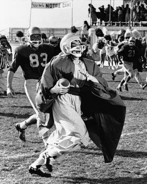 """Actress Shirley MacLaine heads through a field of football players on her 99-yard touchdown run at Rosamond Dry Lake in the Mojave Desert on May 20, 1964, during a scene for the film, """"John Goldfarb, Please Come Home!"""""""