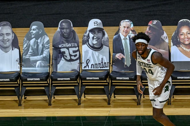 Michigan State's Gabe Brown passes by cutout photos that would be court side seats during the second half of game against Nebraska on Saturday, Feb. 6, 2021, at the Breslin Center in East Lansing.