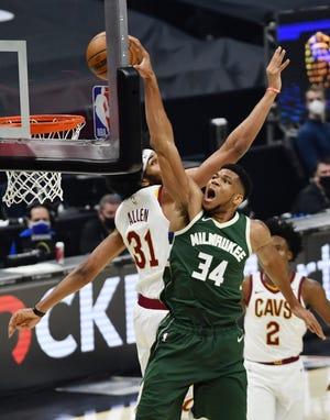 Bucks forward Giannis Antetokounmpo soars past Cavaliers center Jarrett Allen for a dunk during the second quarter.