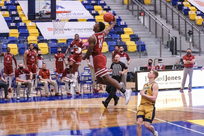 Marcus Watson (14) dunks as the New Mexico State Aggies face off against the Cal Baptist Lancers at Eastwood High School in El Paso on Saturday, Feb. 6, 2021.